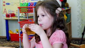 Little beautiful girl drinking tea stock video footage