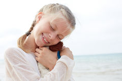 The little beautiful girl embraces an amusing  dog - toy. Favorite soft toy. Stock Photo