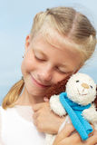 The little beautiful girl embraces an amusing  dog - toy. Favorite soft toy. Stock Images