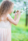 Little beautiful girl enjoying smell of blooming apple tree in a flowering spring garden Stock Photo