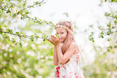 Little beautiful girl enjoying smell in a flowering spring apple garden Royalty Free Stock Images