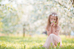 Little beautiful girl enjoying smell in a flowering spring garden Stock Photo