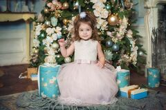 A little beautiful girl with blue eyes in a pink dress sits on the background of a Christmas tree, looks at the camera