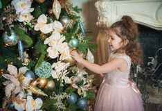 Little beautiful girl with blue eyes in a pink dress is touching the decoration ball on the New Year tree and smiling.