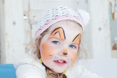 Little beautiful girl with face painting of orange fox stock photo