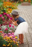Little beautiful girl in flowers park. Photo of little beautiful girl in flowers park Royalty Free Stock Photos