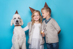 Little beautiful girl and handsome boy with dog celebrate birthday. Friendship. Family. Studio portrait over blue background. Little beautiful girl and handsome royalty free stock images