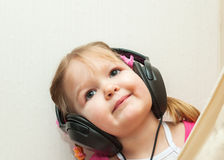 Little beautiful girl in headphones. Listens to music Stock Image