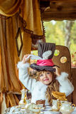 An little beautiful girl holding cylinder hat with ears like a rabbit over head at the table Royalty Free Stock Photos
