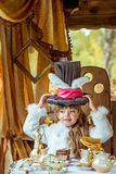 An little beautiful girl holding cylinder hat with ears like a rabbit over head at the table Stock Photos