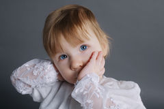 Little beautiful girl holding finger in mouth Royalty Free Stock Photos