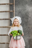 Little beautiful girl holding a pot full of vegetables. Healthy food. Harvest. Little housewife Royalty Free Stock Image