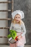 Little beautiful girl holding a pot full of vegetables. Healthy food. Harvest. Little housewife Royalty Free Stock Photography