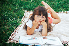 Little beautiful girl lie on grass with book looking at camera. Cute little girl is reading a book while lying on green grass looking to the camera Royalty Free Stock Photo