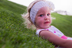 Little beautiful girl lies on the  green grass. Stock Photography