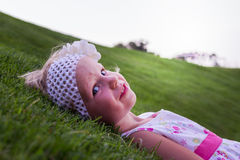 Little beautiful girl lies on the  green grass. Stock Photo
