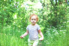 A little beautiful girl with light red hair is walking along a path in the forest stock photography