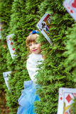 An little beautiful girl in a long blue dress looking from under the fir trees royalty free stock images