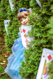 An little beautiful girl in a long blue dress looking from under the fir trees royalty free stock photos