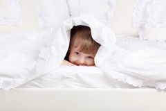 Little beautiful girl looks out from under blanket Stock Images