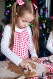 Little beautiful girl making cakes from the molds Stock Image