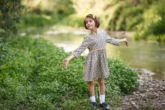 Little girl in nature stream wearing beautiful dress Stock Images