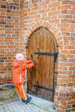 Little beautiful girl opens door in fortress Royalty Free Stock Image