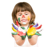 Little beautiful girl and paint. The small beautiful girl has stretched to a camera of a palm soiled in a paint of different colors, smiles, closeup, on white Royalty Free Stock Image