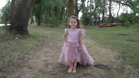 Little beautiful girl in beautiful pink dress with smile on her face walking in nature, slow motion. Family and children concept stock video