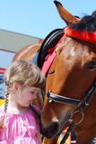 Little beautiful girl in pink dress stands near brown horse Royalty Free Stock Photo