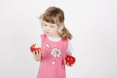 Little beautiful girl in pink eats apple stock photography