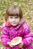 Little beautiful girl in pink holds mushroom Stock Image