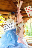 An little beautiful girl playing and dancing with large playing cards on the table Royalty Free Stock Images