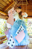 An little beautiful girl playing and dancing with large playing cards on the table Royalty Free Stock Image