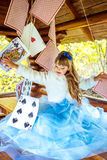 An little beautiful girl playing and dancing with large playing cards on the table royalty free stock photos