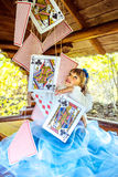 An little beautiful girl playing and dancing with large playing cards on the table stock image