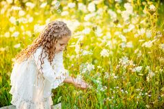 Little beautiful girl playing on the lawn in summer with soap bubbles
