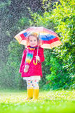 Little beautiful girl playing in the rain Stock Image