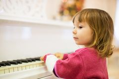 Little beautiful girl is playing on a white grand piano. Little beautiful girl is playing on a white grand piano Stock Photo