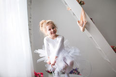 Little beautiful girl and pointe shoes near window. stock images