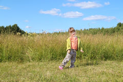 Little beautiful girl poses near tall grass at green meadow Royalty Free Stock Image