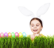 Little beautiful girl with rabbit ears, green grass, colorful eggs. Stock Photos