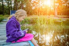 Little beautiful girl read e-books Royalty Free Stock Image