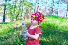 Little beautiful girl in red clothes holding a water bottle. In hand Royalty Free Stock Photography