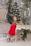Little beautiful girl in a red evening dress the Christmas tree. stock images