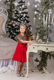 Little beautiful girl in a red evening dress the Christmas tree. Royalty Free Stock Images