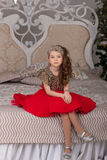 Little beautiful girl in a red evening dress the Christmas tree. royalty free stock photos