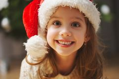 Little beautiful girl with red santa hat stock photos