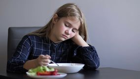 Little beautiful girl refuses to eat while sitting at the table in the kitchen. Children`s whims