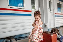 Little beautiful girl in retro dress says goodbye at the station with a little boy in vintage clothes with retro suitcase.  stock photography
